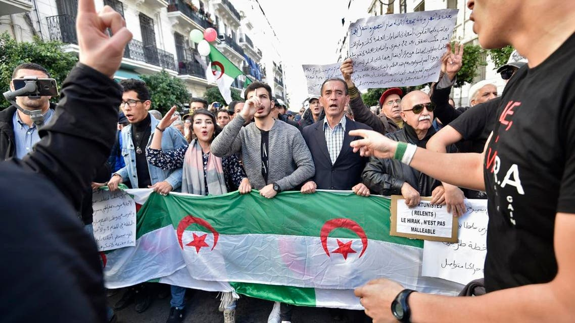 Protesters chant slogans as they march signs and Algerian national flags during an anti-government demonstration in the capital Algiers on December 24, 2019. (AFP)