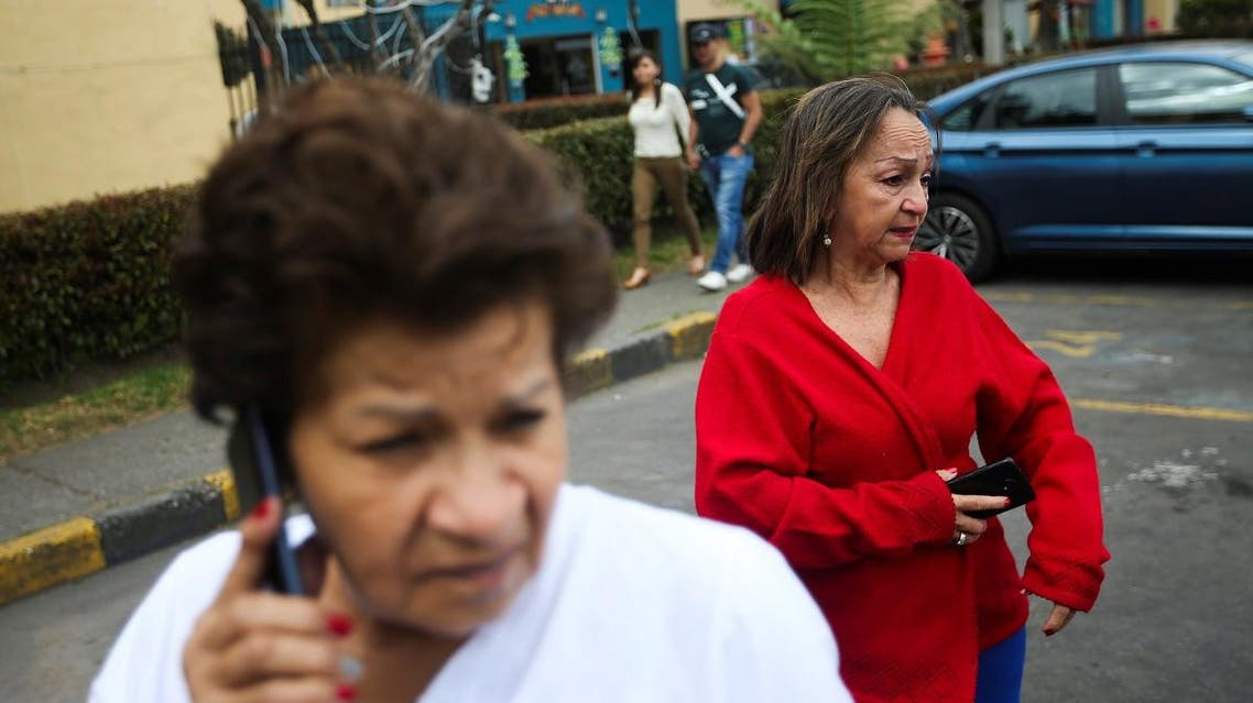 People hold their cellphones as they react after an earthquake in Bogota, Colombia, on December 24, 2019. (Reuters)