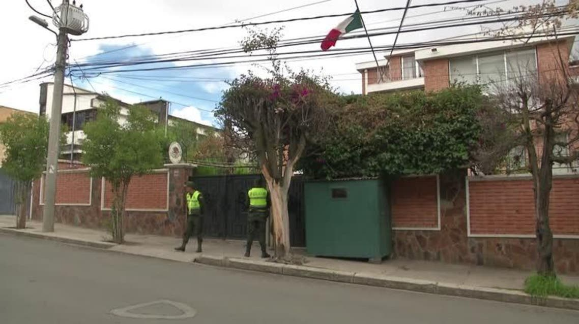 General view of Bolivian police car and police officer at exterior of Mexico's embassy