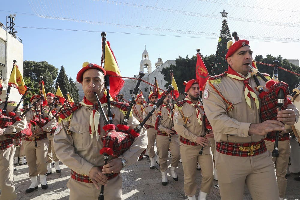 Palestinian scouts perform during a parade at the Manger Square outside the Church of the Nativity in the biblical West Bank city of Bethlehem. (AFP)