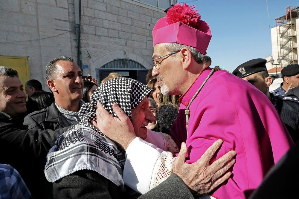 Pierbattista Pizzaballa, apostolic administrator of the Latin Patriarchate of Jerusalem, kisses the head of an elderly Palestinian man in the biblical West Bank city of Bethlehem. (AFP)