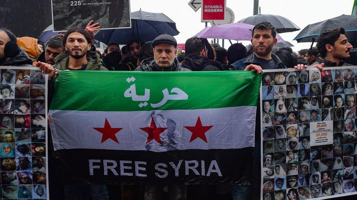 """Protestors hold a Syrian flag and placards reading """"More than 30.000 children killed by Russia and Assad regime"""" and bearing photographs of the victims. (AFP)"""