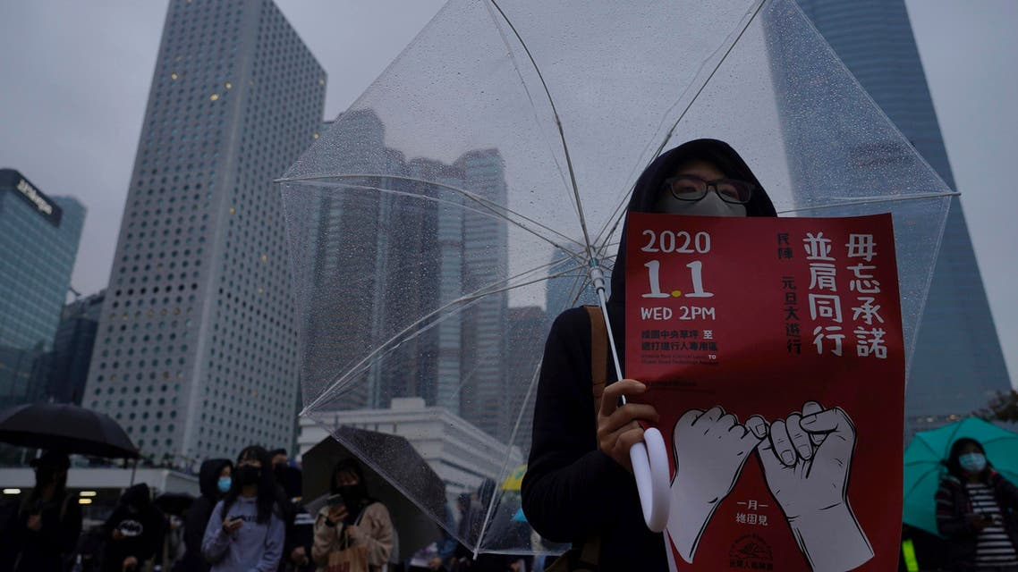 """A protester holds a banner calling for a new year rally with the words """"Don't forget your promises, March Together"""" in Hong Kong on Sunday, Dec. 29, 2019. (Photo: AP)"""