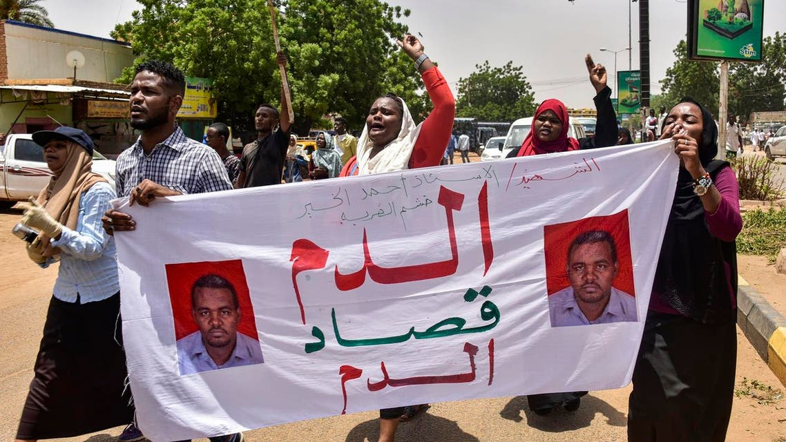 """Demonstrators chant slogans as they march with a banner reading in Arabic """"blood for blood"""" outside a courthouse complex in the Sudanese capital's twin city of Omdurman on August 21, 2019 during the trial of 40 members of Sudan's now-dissolved National Intelligence and Security Service facing charges over the death in custody of Ahmed al-Kheir, a teacher from the eastern town of Khashma el-Girba, in the early days of the wave of nationwide protests that eventually brought longtime ruler Omar al-Bashir. (photo: AFP)"""