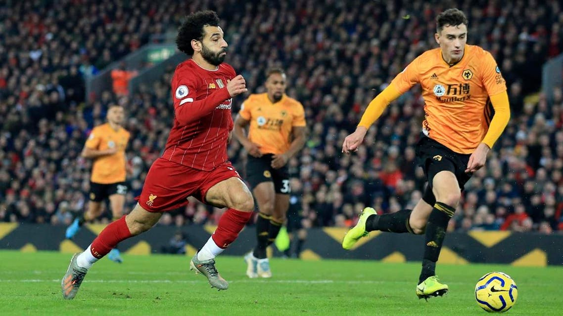 Liverpool's Mohamed Salah (left), runs with the ball during the English Premier League soccer match against Wolverhampton Wanderers at Anfield Stadium, Liverpool, England, on December 29, 2019. (AP)