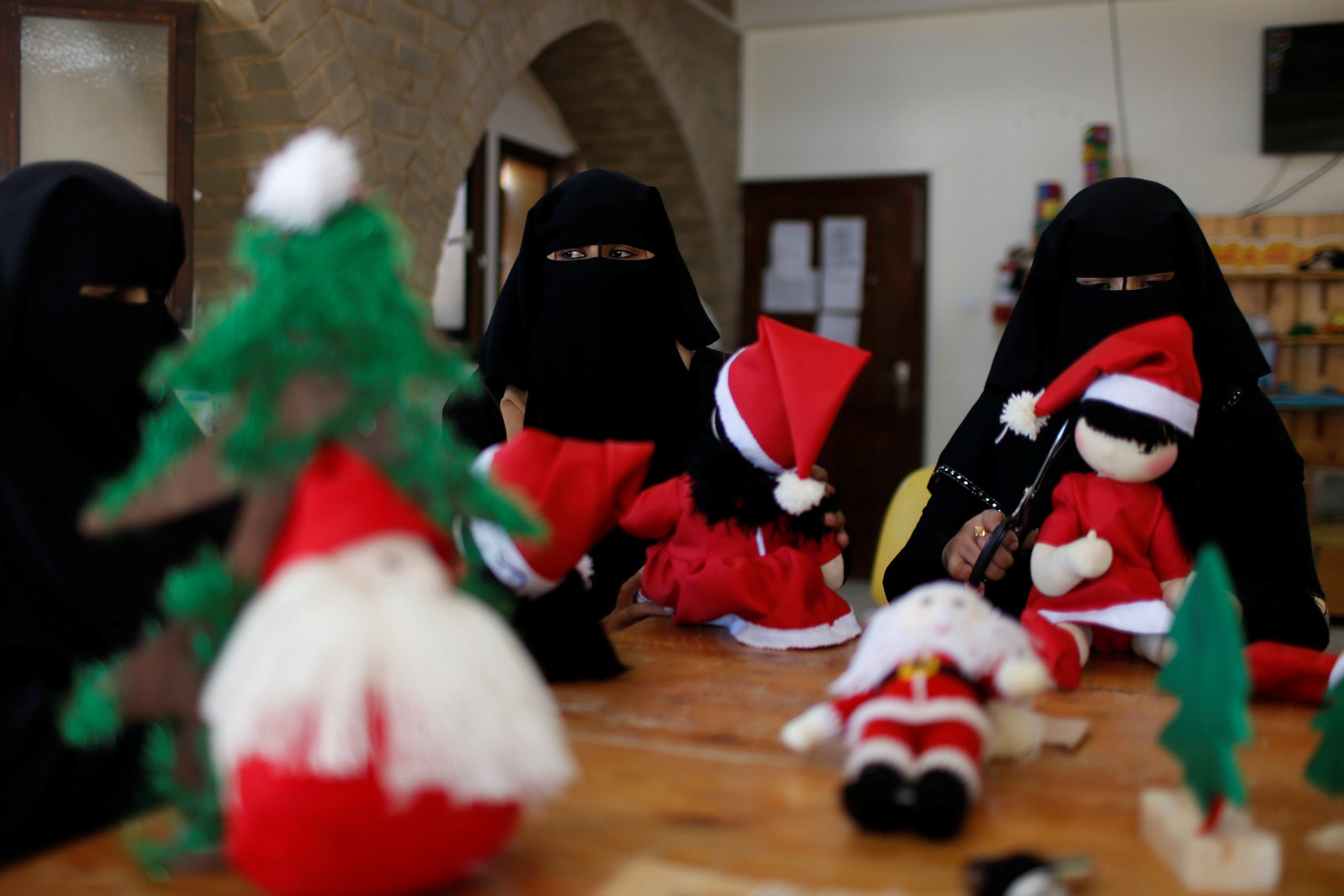 Palestinian women wearing face veil, niqab, make Santa-themed Christmas toys in the northern Gaza Strip December 29, 2019. Picture taken December 29, 2019. REUTERS