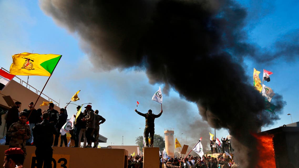 Protesters burn property in front of the U.S. embassy compound, in Baghdad, Iraq, Tuesday, Dec. 31, 2019.