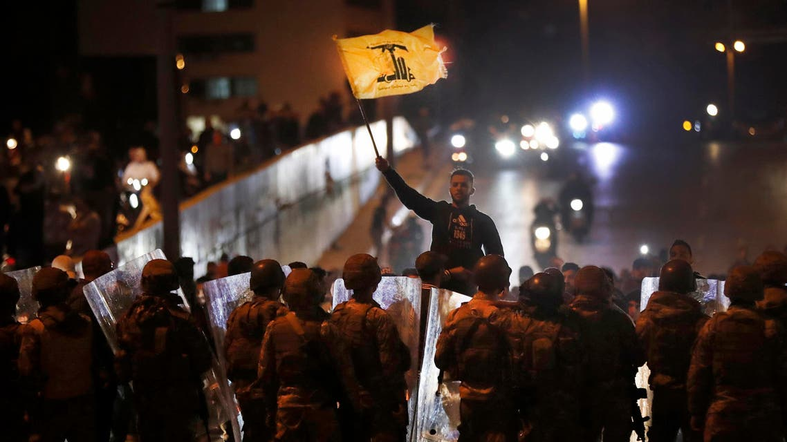 A supporter of the Iran-backed militant Hezbollah group waves his group's flag as he stands in front of Lebanese army soldiers after a clash erupted between the anti-government protesters and the group, in Beirut, Lebanon, early Monday, Nov. 25, 2019. (AP)