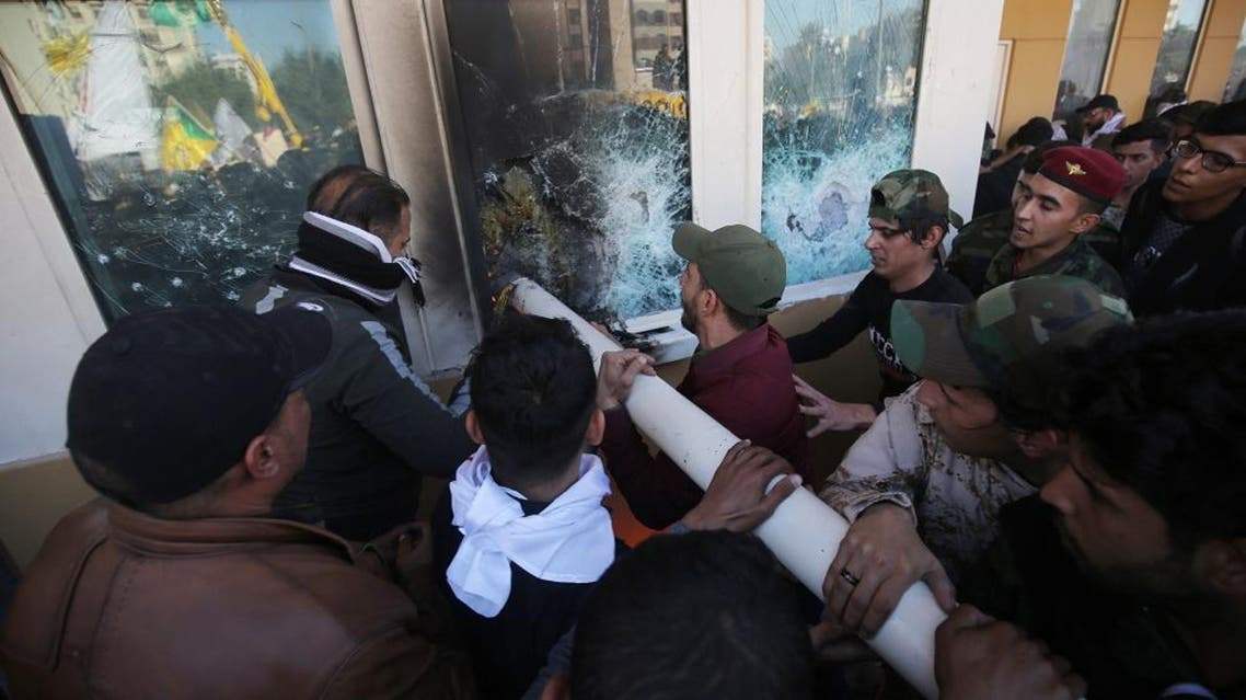 Iraqi protesters use a plumbing pipe to break the bullet-proof glass of the US embassy's windows in Baghdad. (AFP)