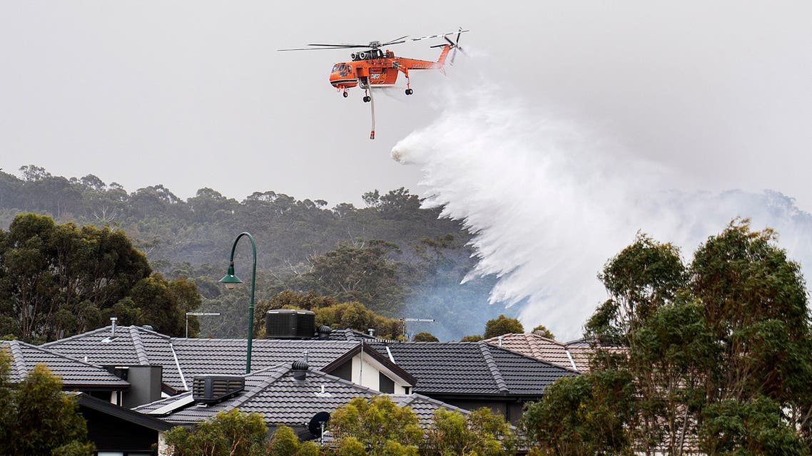 A skycrane drops water on a bushfire in scrub behind houses in Bundoora, Melbourne, Monday, Dec. 30, 2019. (AP)