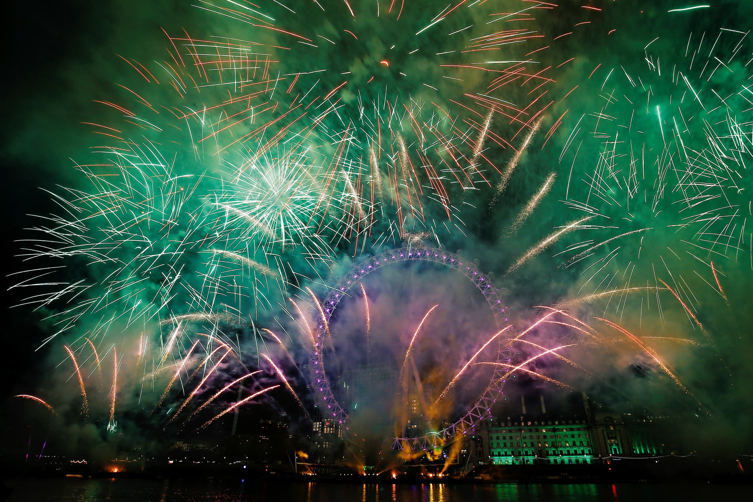Fireworks explode over the London Eye wheel during New Year celebrations in central London (AP)