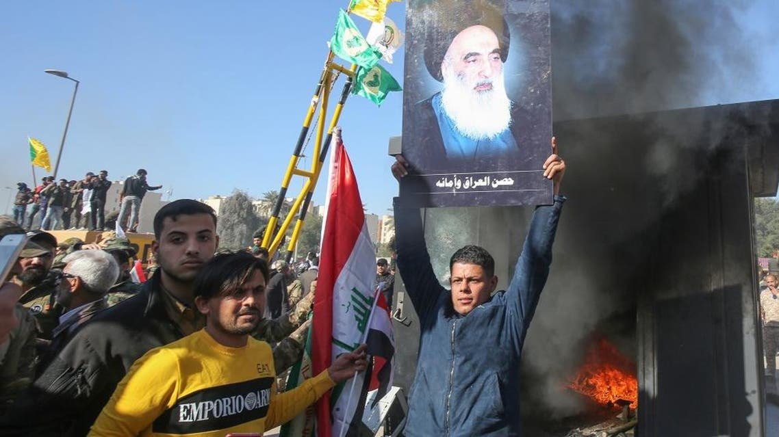 An Iraqi supporter of the PMF lifts a picture of Iraq's top Shia cleric Grand Ayatollah Ali Sistani. (AFP)