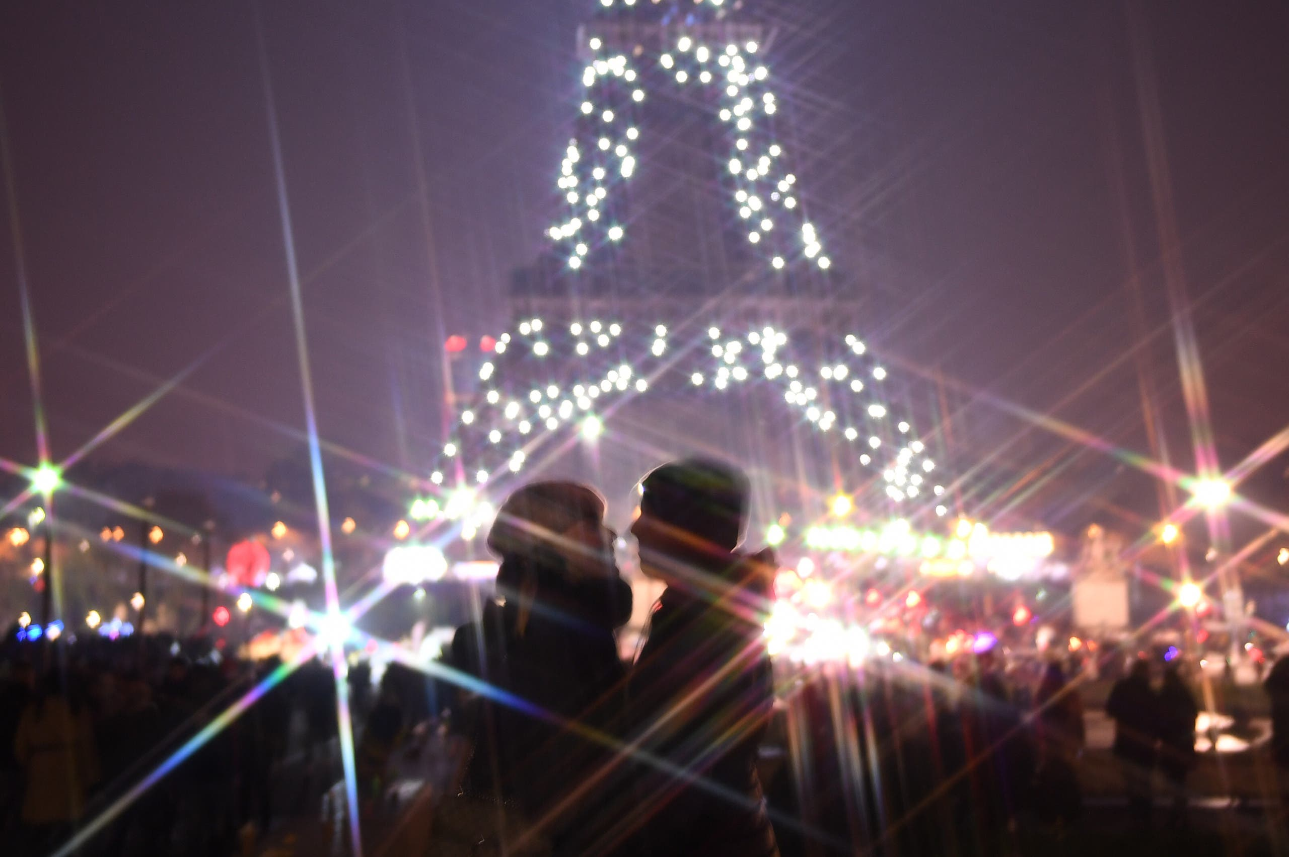 A couple in front of the Eiffel tower during the New Year's celebrations in Paris. (Photo: AFP)