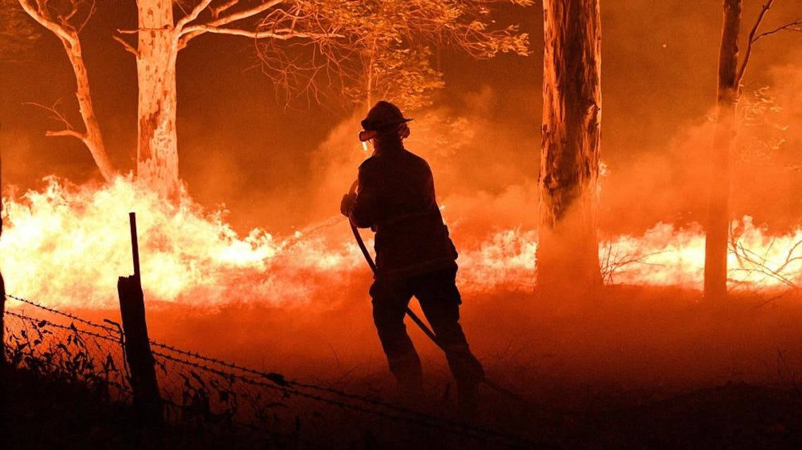 A firefighter hosing down trees and flying embers in an effort to secure nearby houses from bushfires in Australia. (AFP)