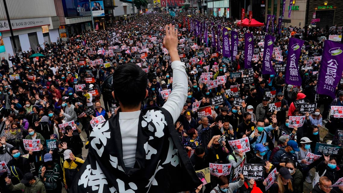 A protestor shows five demands gesture as Hong Kong people participate in their annual pro-democracy march in Hong Kong, Wednesday, Jan. 1, 2020. (AP)