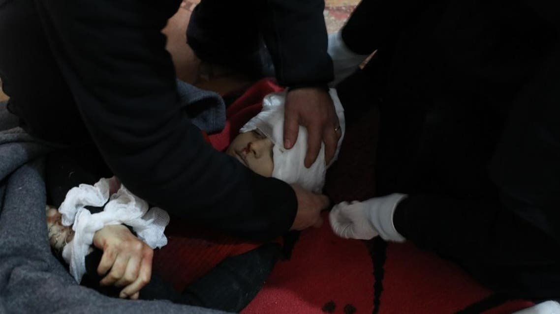 Medics wrap the body of a boy, who was killed following a missile fired by Syrian regime forces. (AFP)