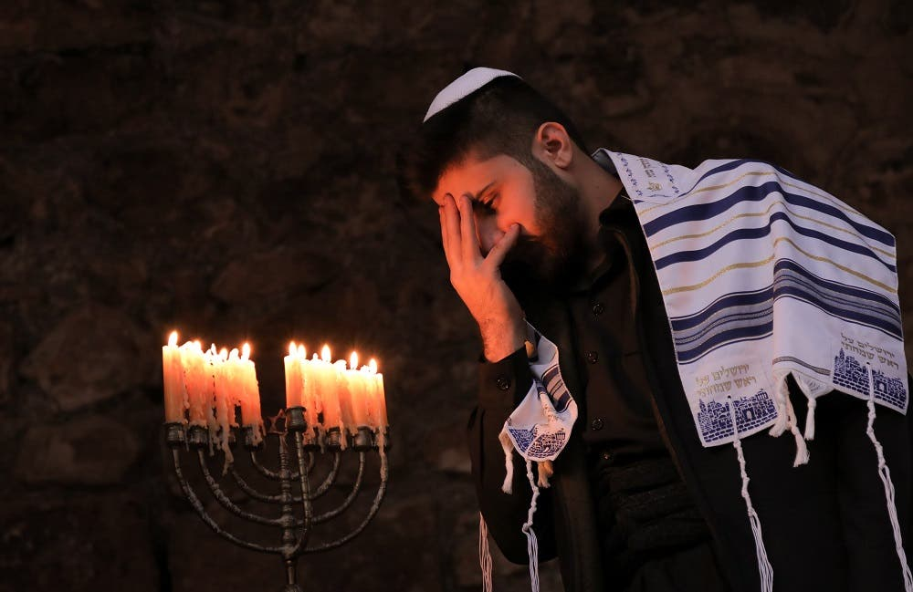 A member of Iraq's Kurdish Jewish community takes part in a ceremony on the last night of the Jewish holiday of Hanukkah. (AFP)