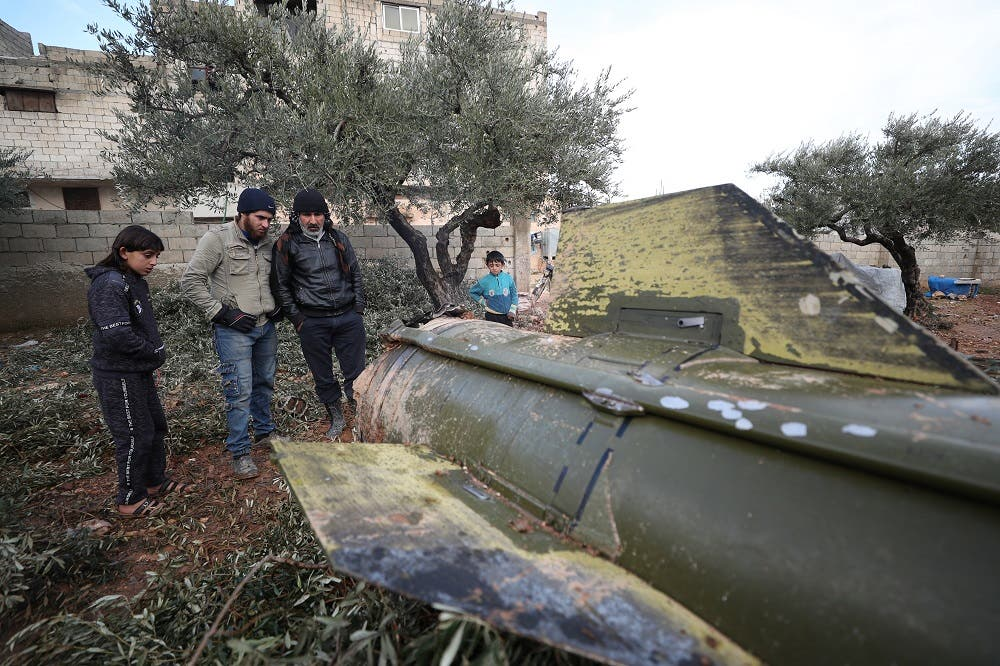 People gather around the remains of a missile, fired by Syrian regime forces. (AFP)