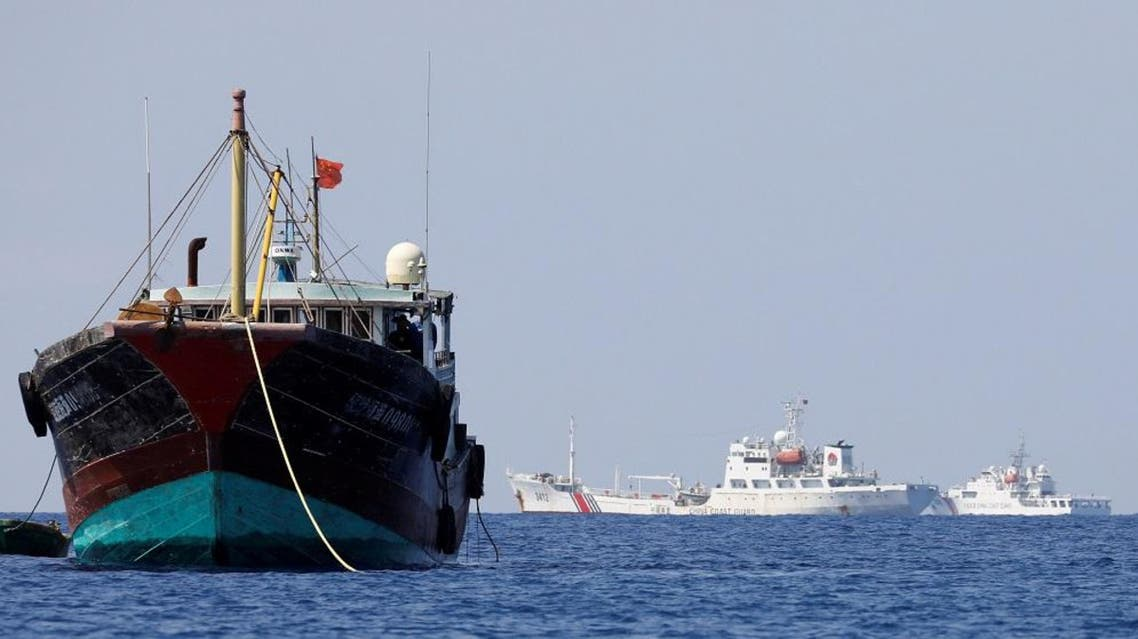 China Coast Guard vessels patrol past a Chinese fishing vessel at the disputed Scarborough Shoal. (File photo: Reuters)