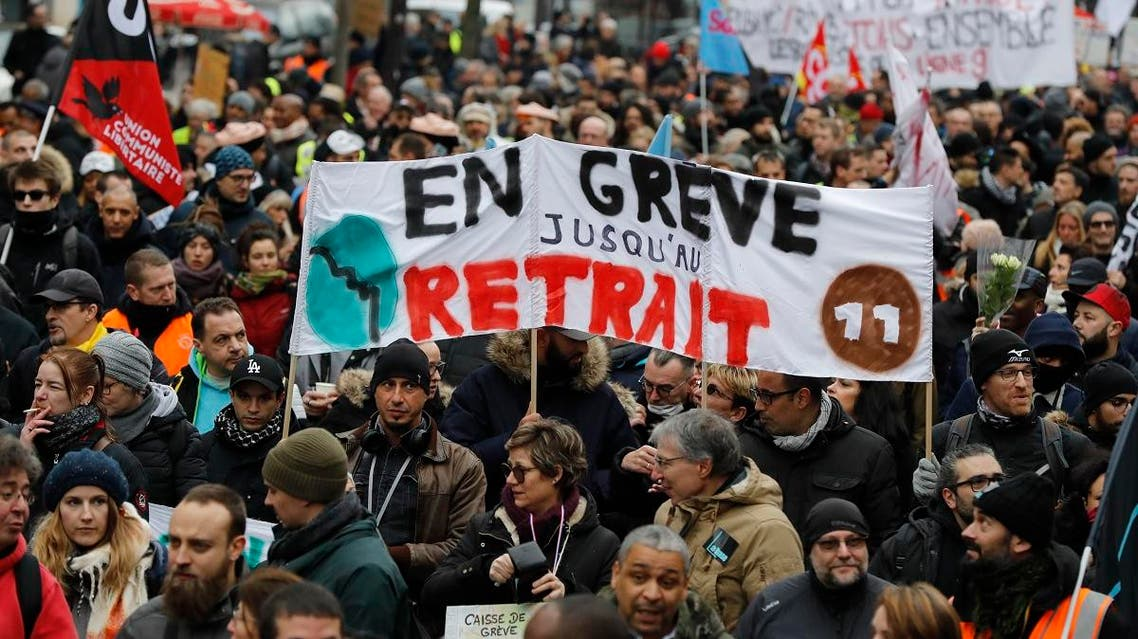 """People hold a banner reading """"On strike untill withdrawal"""" during a demonstration called by French national trade union General Confederation of Labour (CGT) against the pension reform on January 4, 2020, in Paris. (AFP)"""