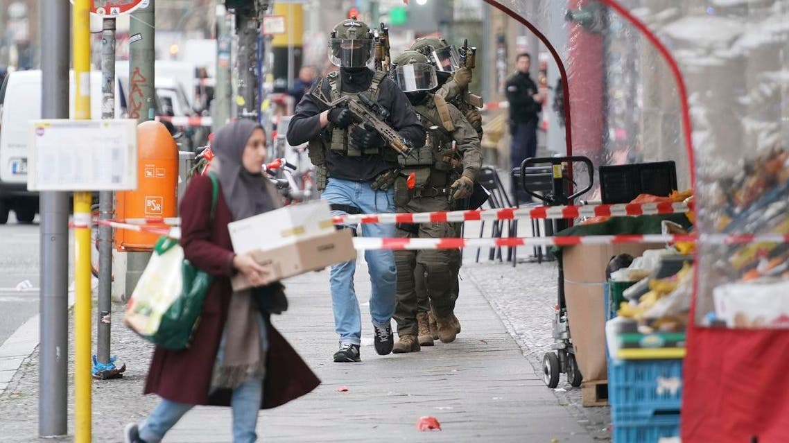 Police officers of the SWAT Team SEK walk over the Kochstrasse during a police operation near the former Checkpoint Charlie in Berlin, Germany, Monday, Dec. 30, 2019. (AP)