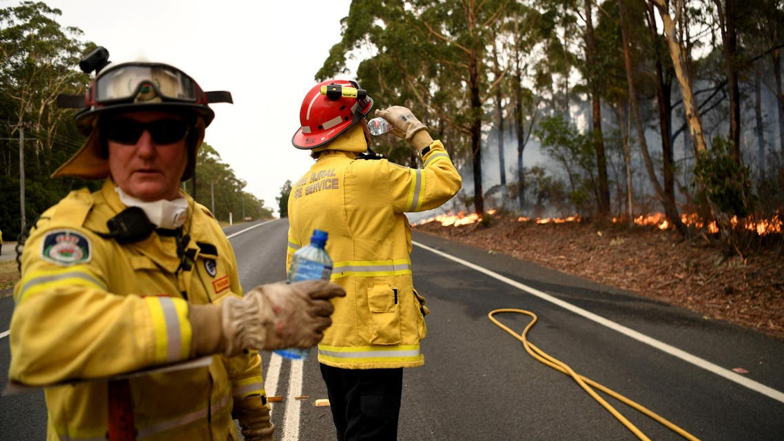 Firefighters keep a watchful eye on a fire threatening homes along the Princes Highway near in Milton, Australia January 5, 2020. (Reuters)