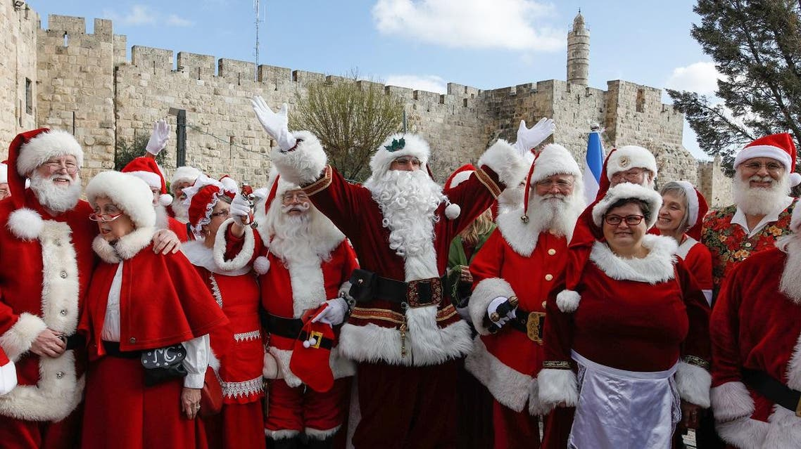 A group of some 50 people dressed in Santa Claus from various countries around the world visits the old city of Jerusalem on January 05, 2020. (AFP)