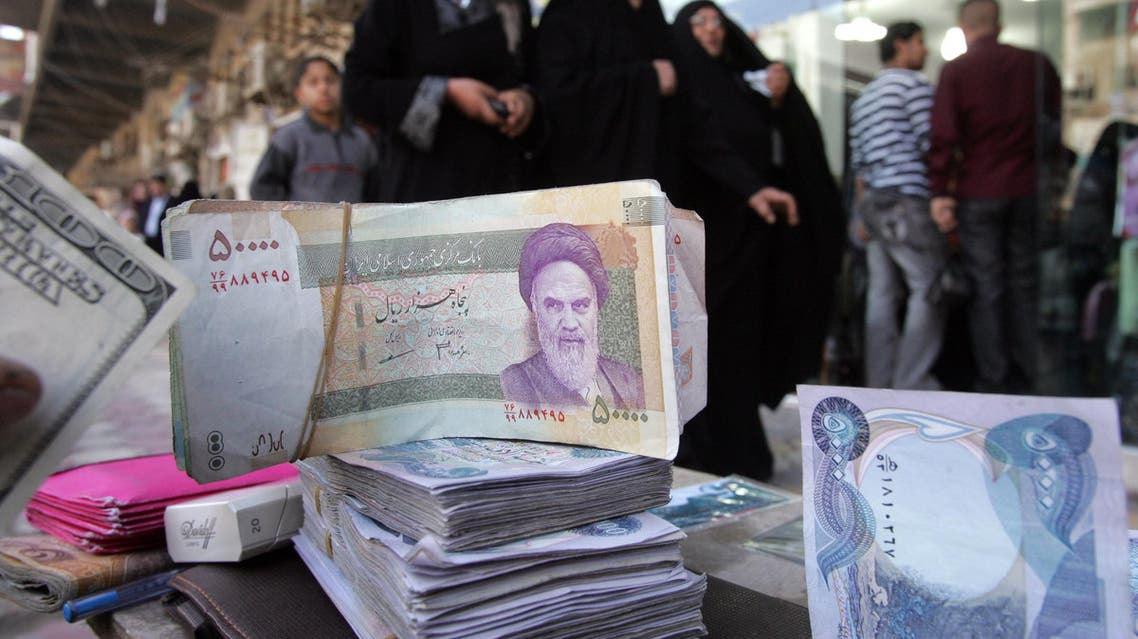 Iranian (C), Iraqi (R) and US (L) currency is on display at a money changers station. (File photo: AFP)