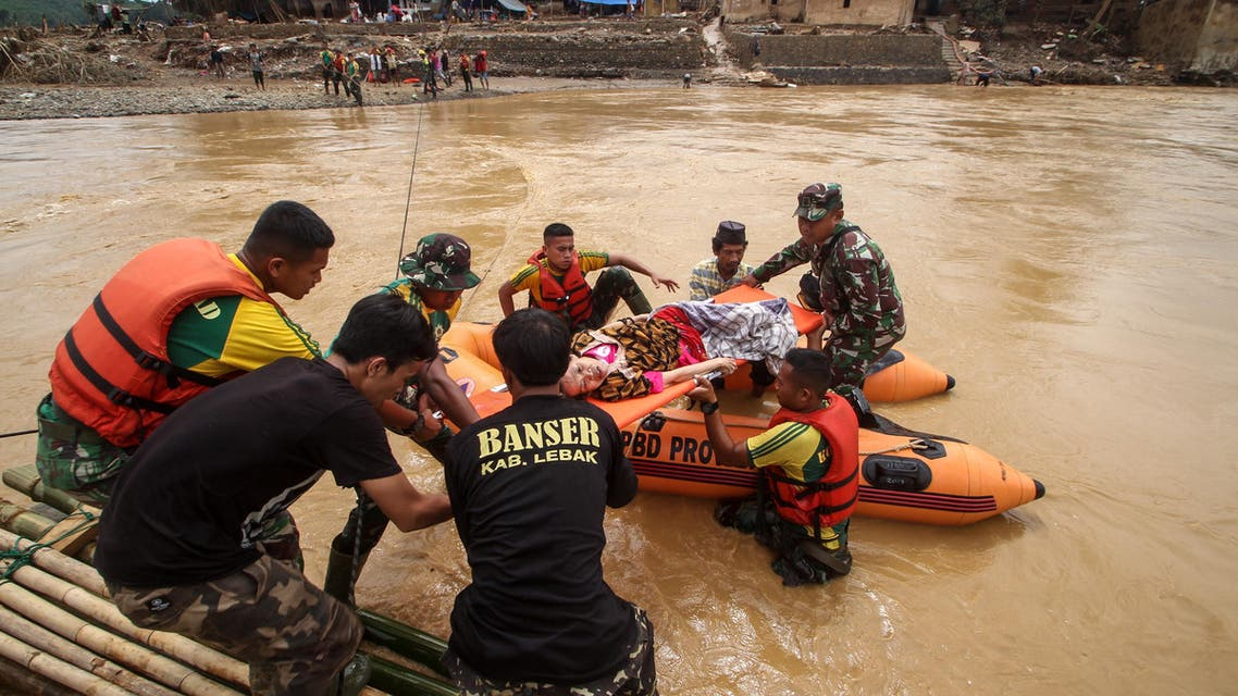 Rescuers help a sick woman cross the river to get medical assistance at the Sukarame village in Lebak. (AFP)