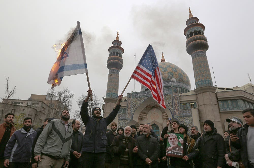 Iranians burn an Israeli and a US flag during an anti-US protest over the killing of Qassem Soleimani. (AFP)