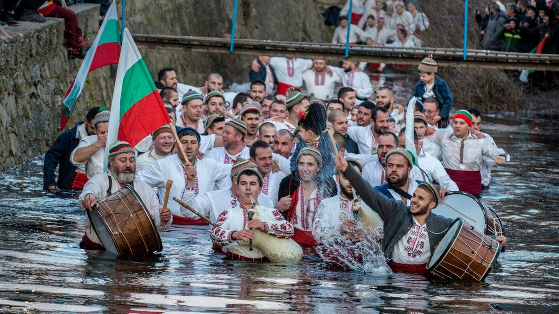 Bulgarians sing, play bagpipes and chain dance in icy waters during Epiphany in Kalofer on Jan. 6, 2020. (Photo: AP)
