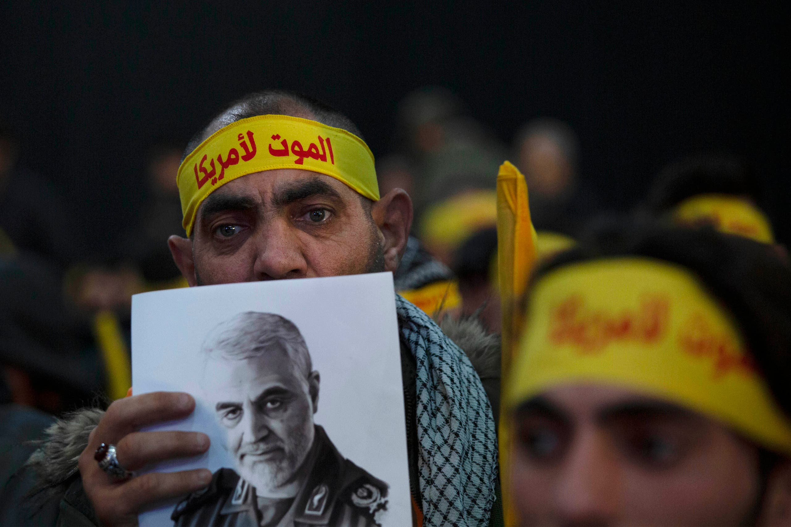 A supporter of Hezbollah leader Sayyed Hassan Nasrallah holds a portrait of slain Iranian Revolutionary Guard Gen. Qassem Soleimani before a televised speech by Nasrallah in a southern suburb of Beirut, Lebanon, Sunday, Jan. 5, 2020 following the U.S. airstrike in Iraq that killed Soleimani. His headband reads: death to America. (AP)
