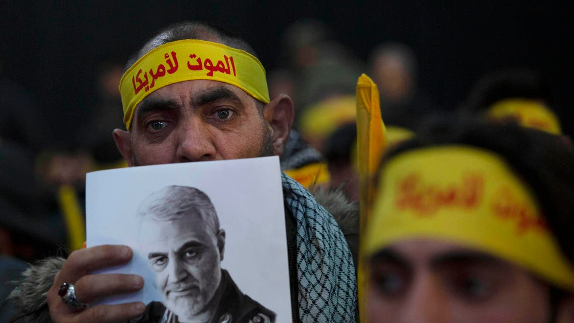 """A supporter of Hezbollah leader Sayyed Hassan Nasrallah holds a portrait of slain Iranian Revolutionary Guard Gen. Qassem Soleimani before a televised speech by Nasrallah in a southern suburb of Beirut, Lebanon, Sunday, Jan. 5, 2020 following the U.S. airstrike in Iraq that killed Soleimani. His headband reads: """"death to America."""" (AP Photo"""
