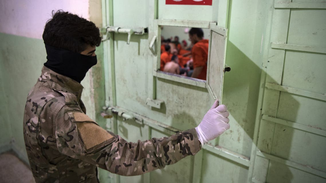 A member of the Syrian Democratic Forces (SDF) stands guard in a prison where men suspected to be afiliated with the Islamic State (IS) group are jailed in northeast Syria in the city of Hasakeh on October 26, 2019. Kurdish sources say around 12,000 IS fighters including Syrians, Iraqis as well as foreigners from 54 countries are being held in Kurdish-run prisons in northern Syria.