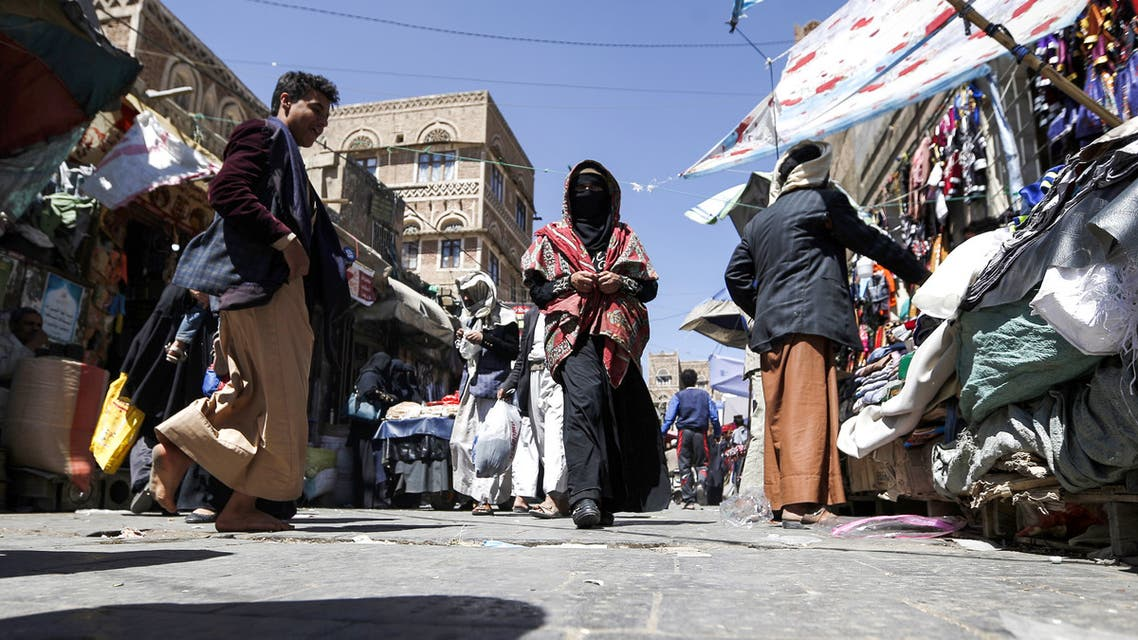 A Yemeni woman wearing a veil walks past stalls down the market in the old city of the capital Sanaa on February 15, 2018.