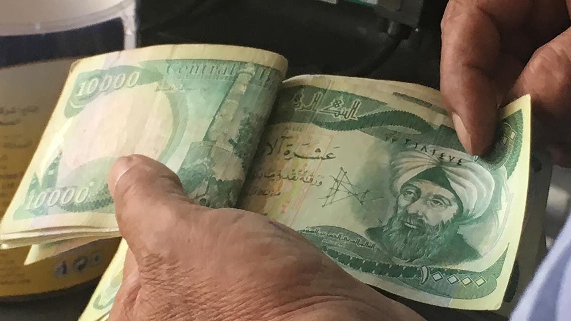 """An Iraqi policeman pays for groceries with 10,000-Iraqi dinar banknotes bearing an image of Mosul's iconic leaning minaret, known as the """"Hadba"""" (Hunchback), on June 22, 2017, in the capital Baghdad. Iraqi officials say jihadists have blown up Mosul's iconic minaret and the mosque where the Islamic State group's leader appeared in 2014 and urged Muslims to join his """"caliphate"""". The Islamic State group (IS) says the Nuri mosque, where jihadist supremo Abu Bakr al-Baghdadi gave his first sermon as """"caliph"""", was destroyed by a US air strike. Ali CHOUKEIR / AFP"""
