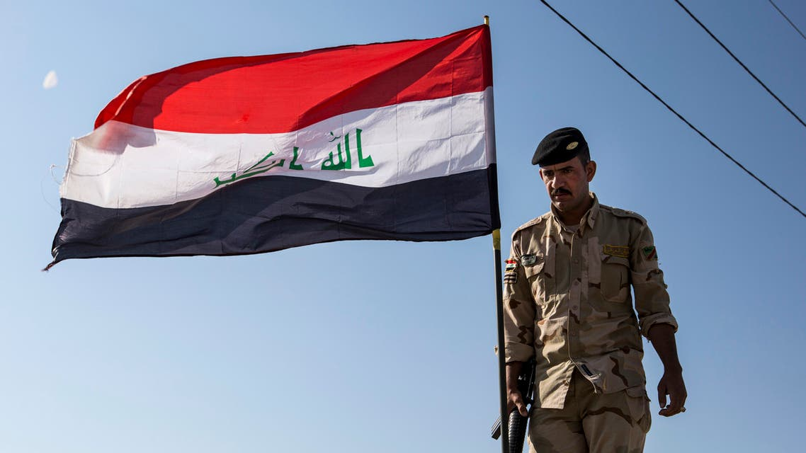 An Iraqi soldier stands next to a flying national flag atop an infantry-fighting vehicle (IFV) near a demonstration outside the southern port of Umm Qasr on November 5, 2019, after security forces attempted to break up crowds blocking the road to the port.
