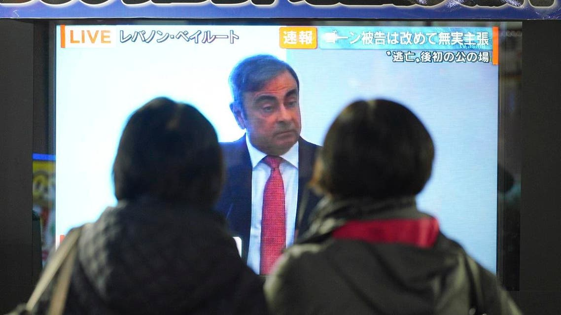 People in Tokyo watch a public TV showing a live broadcast of former Nissan chairman Carlos Ghosn speaking from Lebanon at his press conference Wednesday, Jan. 8, 2020. (AP)