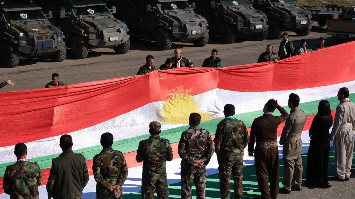 Members of the Iraqi Kurdish Peshmerga forces hold up a giant Kurdish flag to commemorate the annual Kurdish Flag Day. (File photo: AFP)