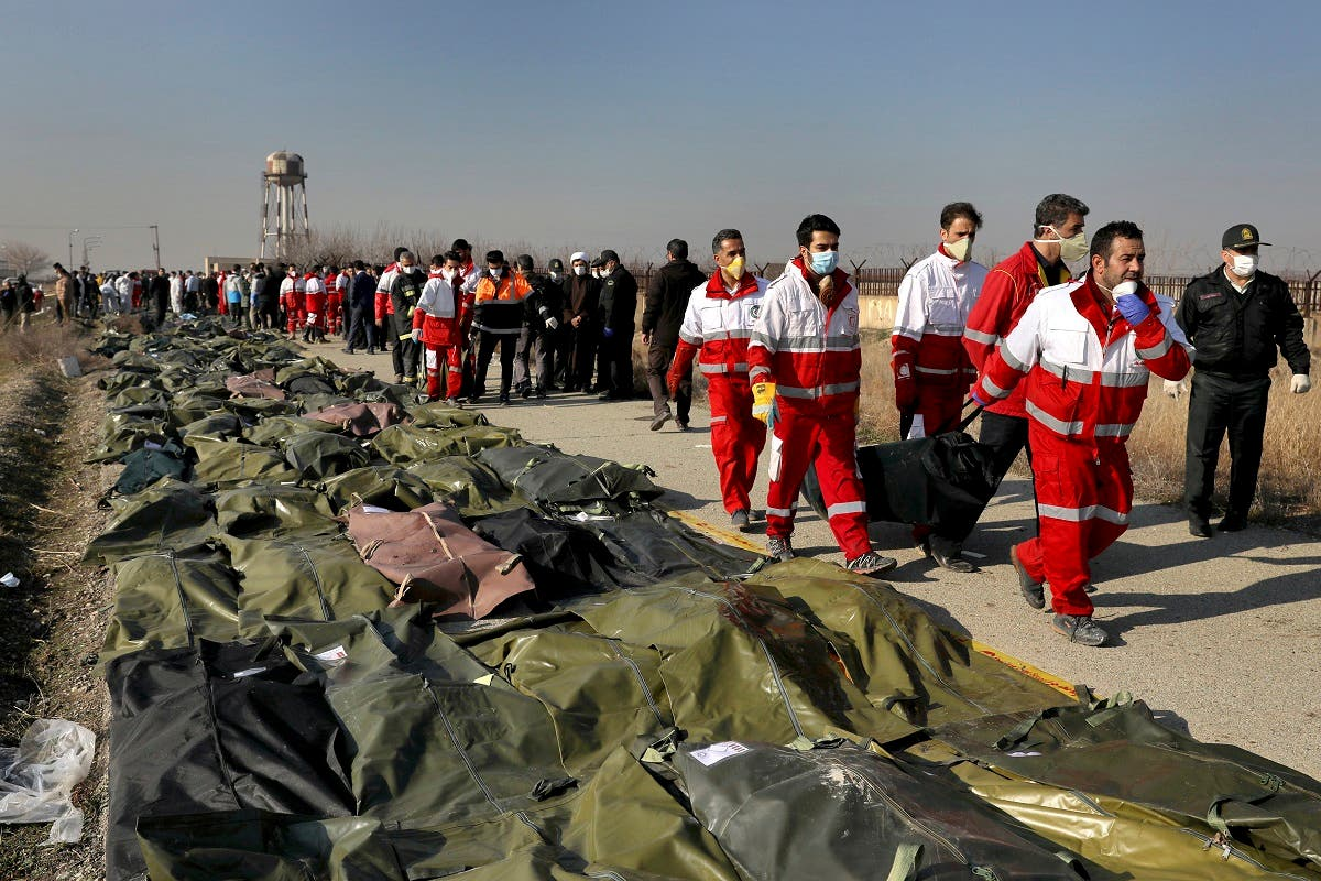 Rescue workers carry the body of a victim of a Ukrainian plane crash in Shahedshahr, southwest of the capital Tehran, Iran, Wednesday, Jan. 8, 2020. (AP)
