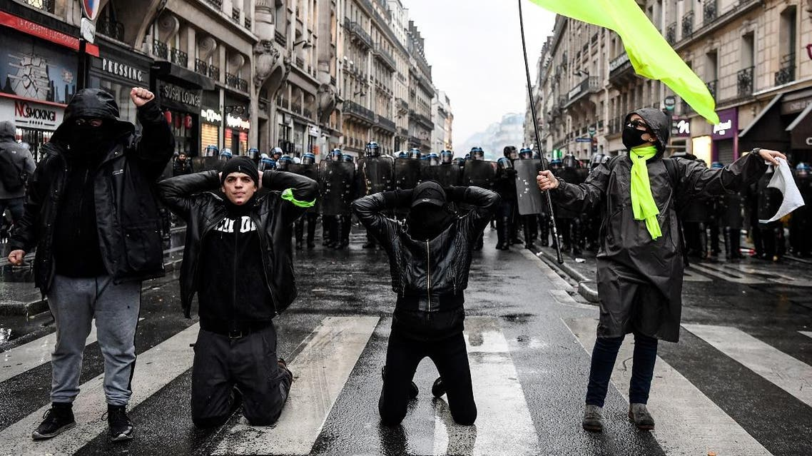 Protesters kneel and gestures in front of a police cordon during a demonstration in Paris, on January 9, 2020, on the 36th day of a nationwide multi-sector strike against French government's pensions overhaul. (AFP)