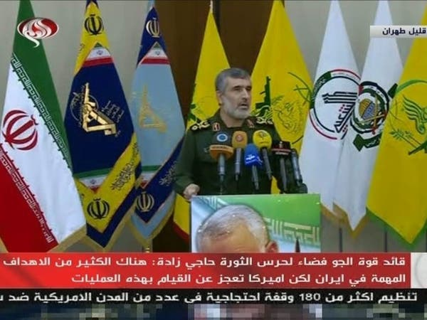 قائد بالحرس الثوري يظهر وخلفه أعلام الميليشيات التابعة لطهران