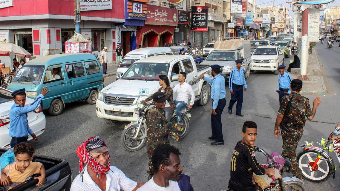 Yemeni policemen (in blue) and Huthi fighters control the traffic at the centre of the port city of Hodeidah, around 230 kilometres west of the capital Sanaa, on May 13, 2019. The United Nations said on May 12, 2019 that a Yemeni rebel withdrawal from key Red Sea ports was proceeding as planned, after the government accused the insurgents of faking the pullout.
