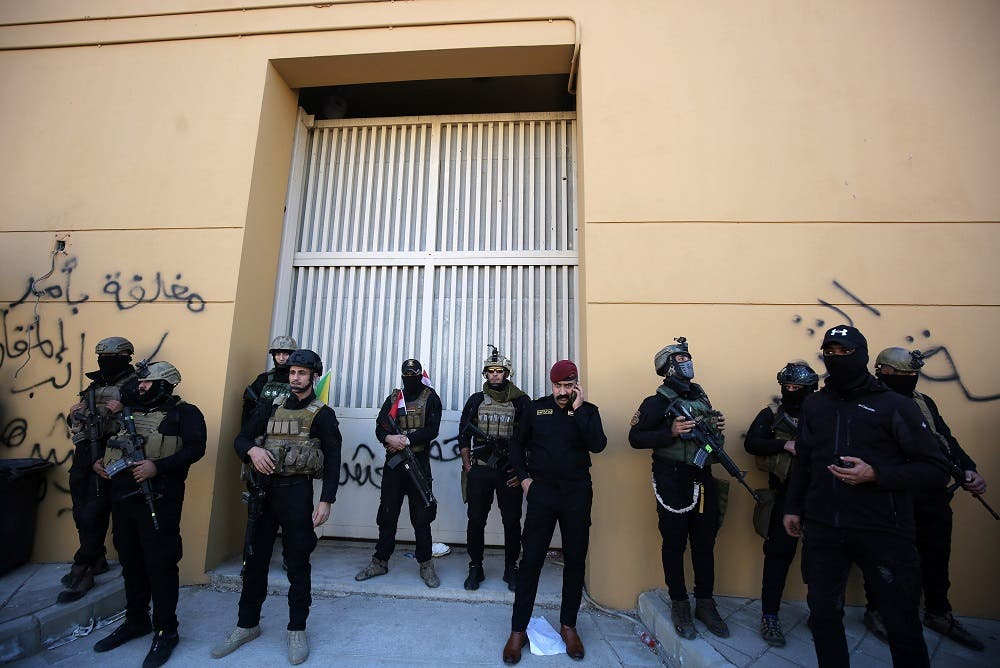 Members of Iraq's security forces stand guard outside one of the gates of the US embassy in Baghdad's Green Zone. (AFP)