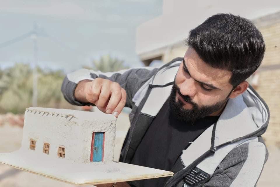الشاب كرار محمد مع مجسم من صنعه