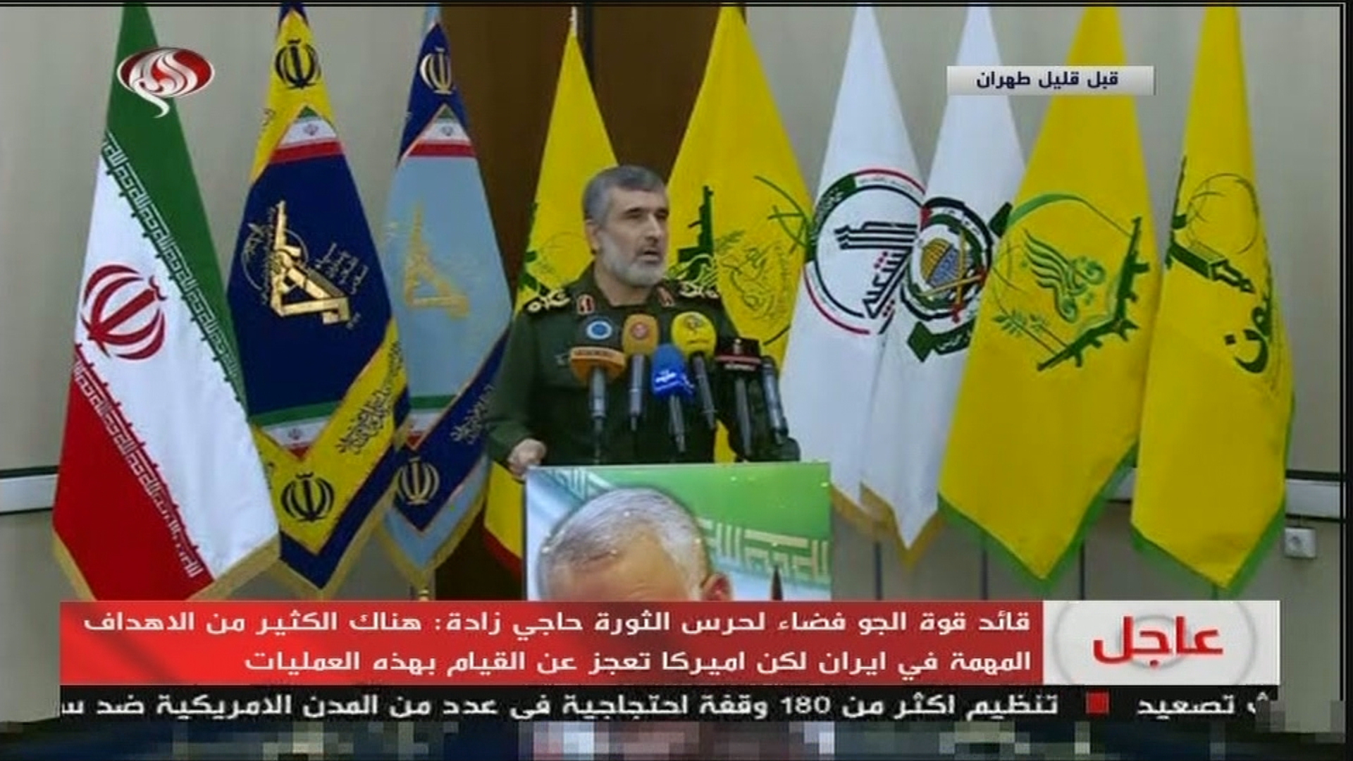 IRGC airforce commander Amir Ali Hajizadeh appears on state TV in front of proxy flags including the PMU militia flag, January 9. (Screengrab from Twitter)