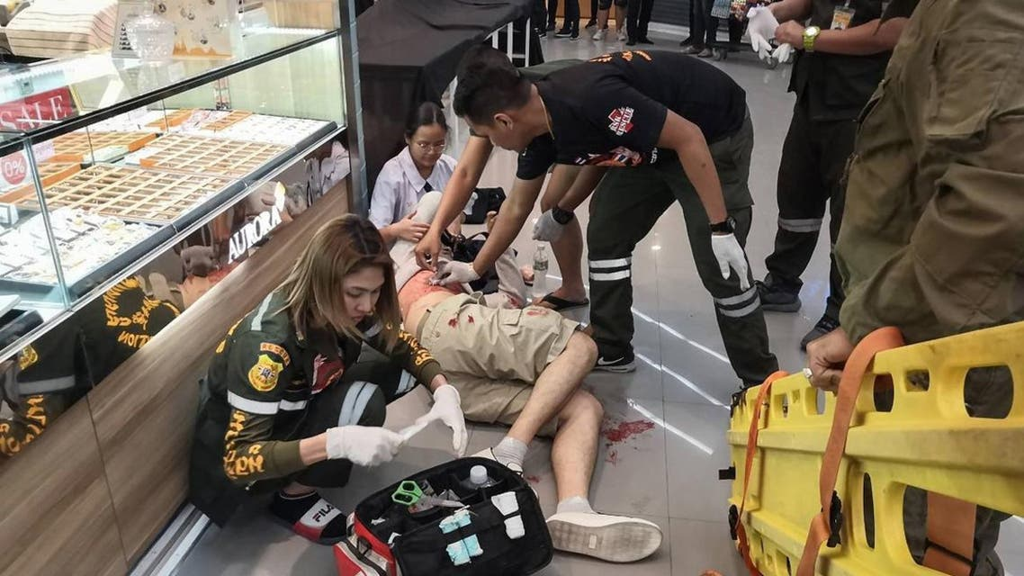 Paramedics helping a man wounded during a robbery at a shopping mall in the town of Lopburi. A masked gunman killed three people including a two-year-old child and wounded four. (Photo: AFP)
