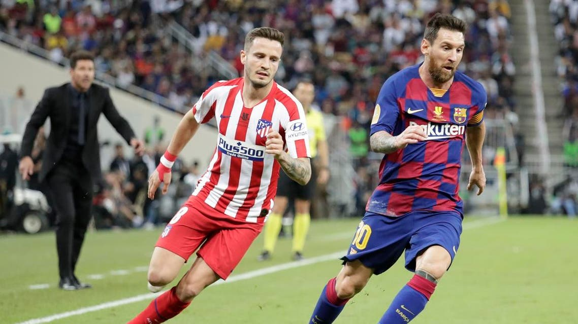 Barcelona's Lionel Messi controls the ball past Atletico Madrid's Saul during the Spanish Super Cup semifinal soccer match between Barcelona and Atletico Madrid at King Abdullah stadium in Jeddah, Saudi Arabia. (AP)