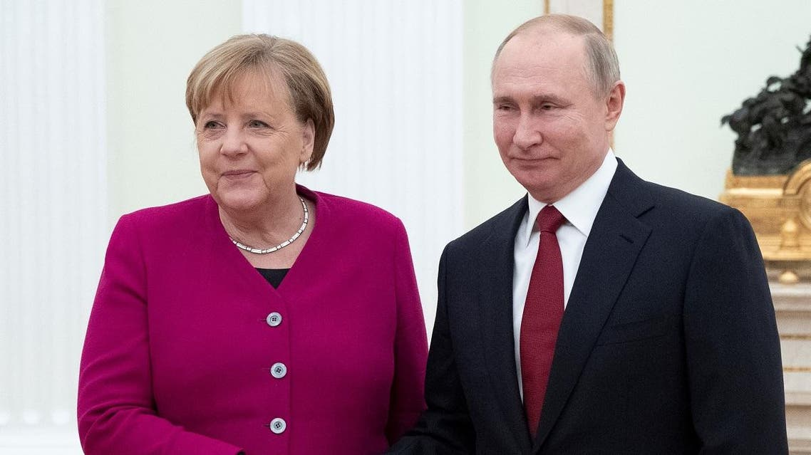 Russian President Vladimir Putin (R) welcomes and shakes hands with German Chancellor Angela Merkel (L) as they pose for a photo prior to their meeting at the Kremlin in Moscow, on January 11, 2020. (AFP)