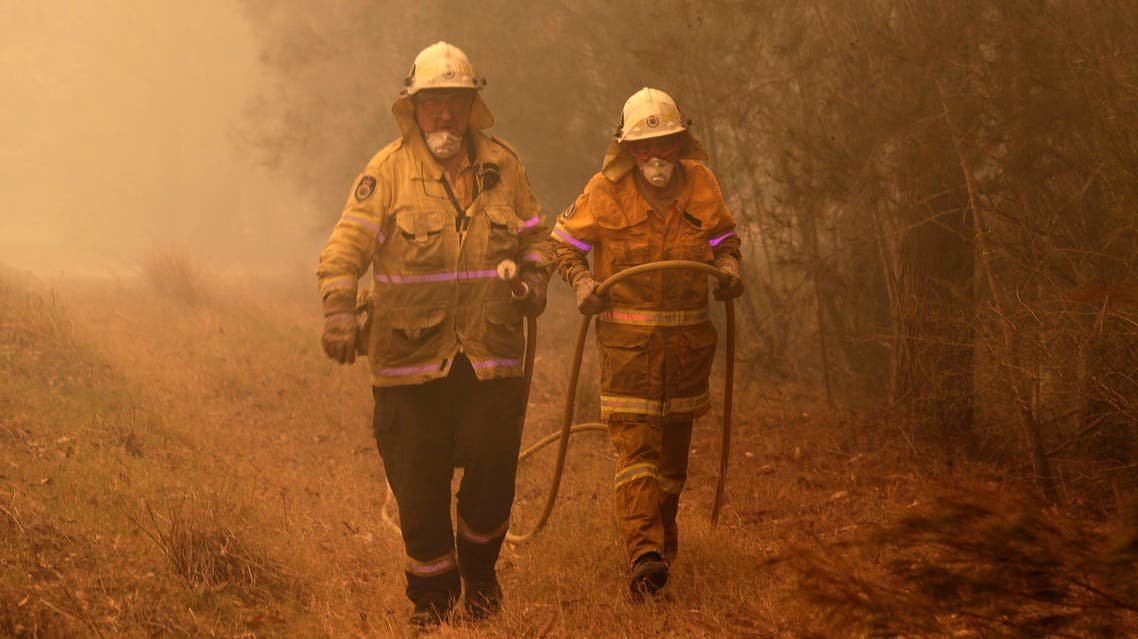 Firefighters drag their water hose after putting out a spot fire near Moruya, Australia (AP)